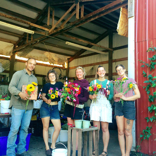 Five Persephone farmers posing with flowers